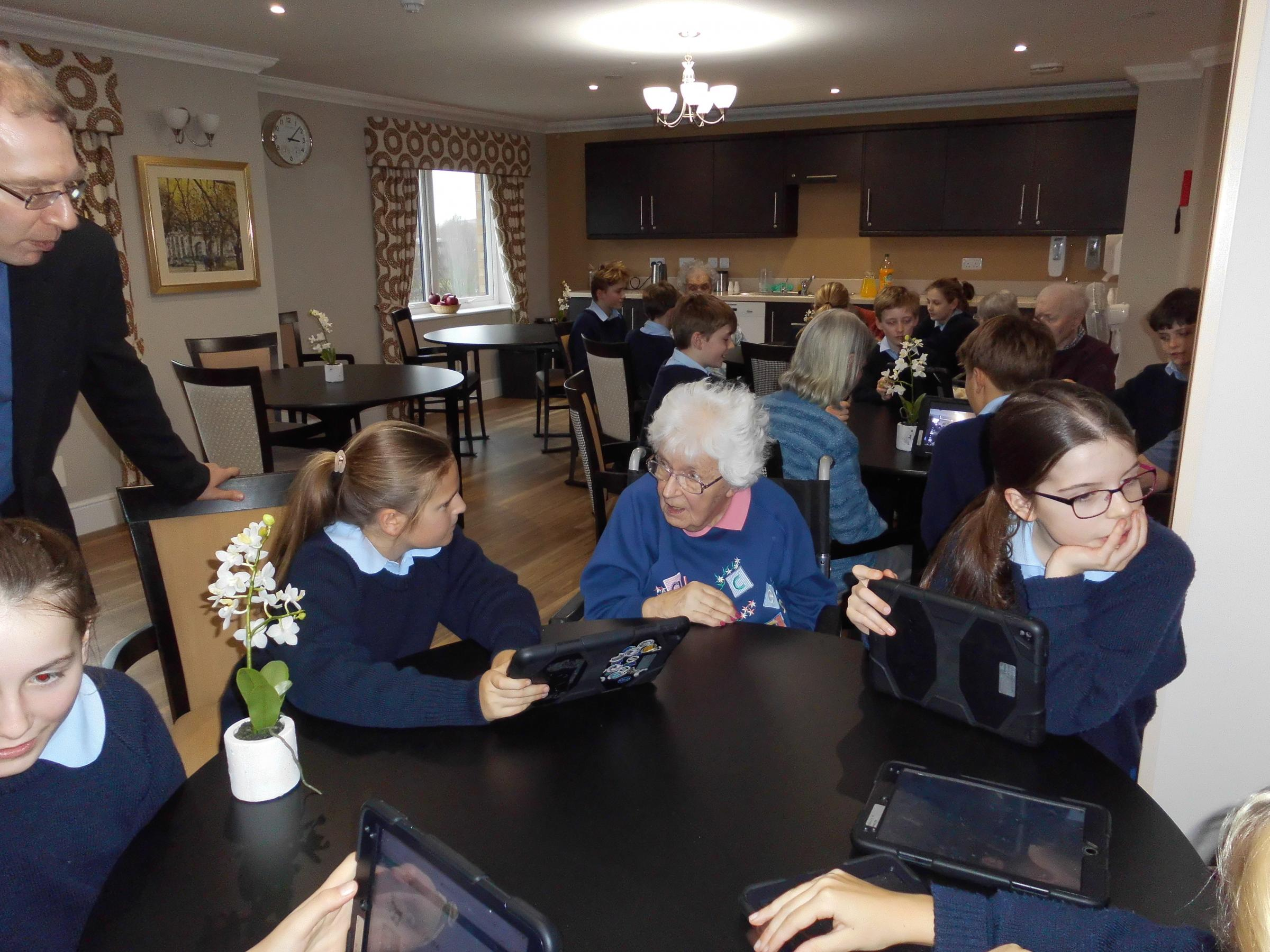 Students showing Harrier Grange residents how to use an iPad