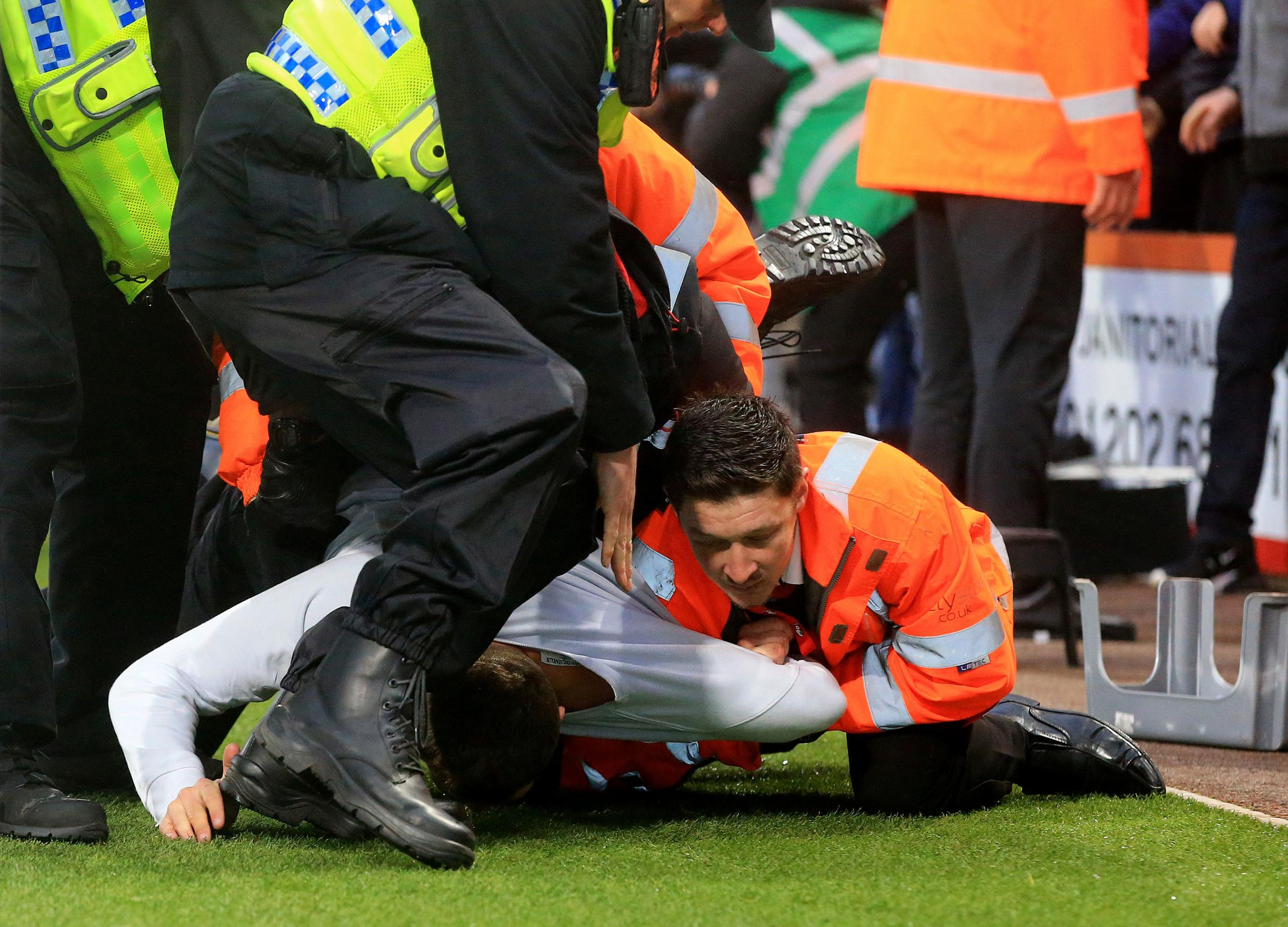 A Newcastle United fan is removed from the pitch by stewards and police after invading the pitch during the Premier League match at the Vitality Stadium, Bournemouth. PRESS ASSOCIATION Photo. Picture date: Saturday March 16, 2019. See PA story SOCCER Bou