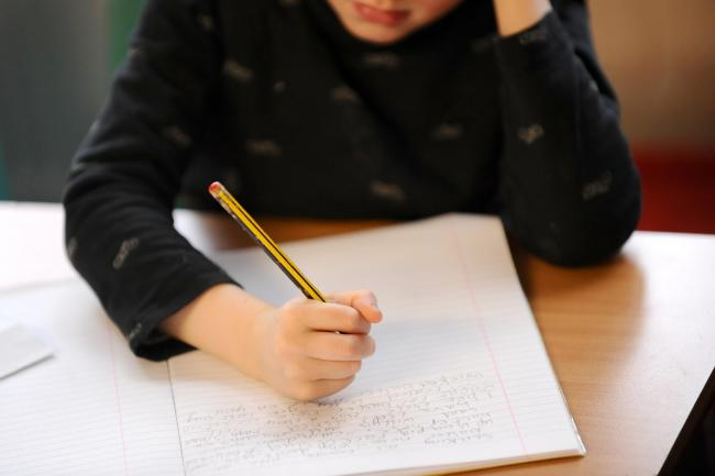 A pupil writing in a jotter