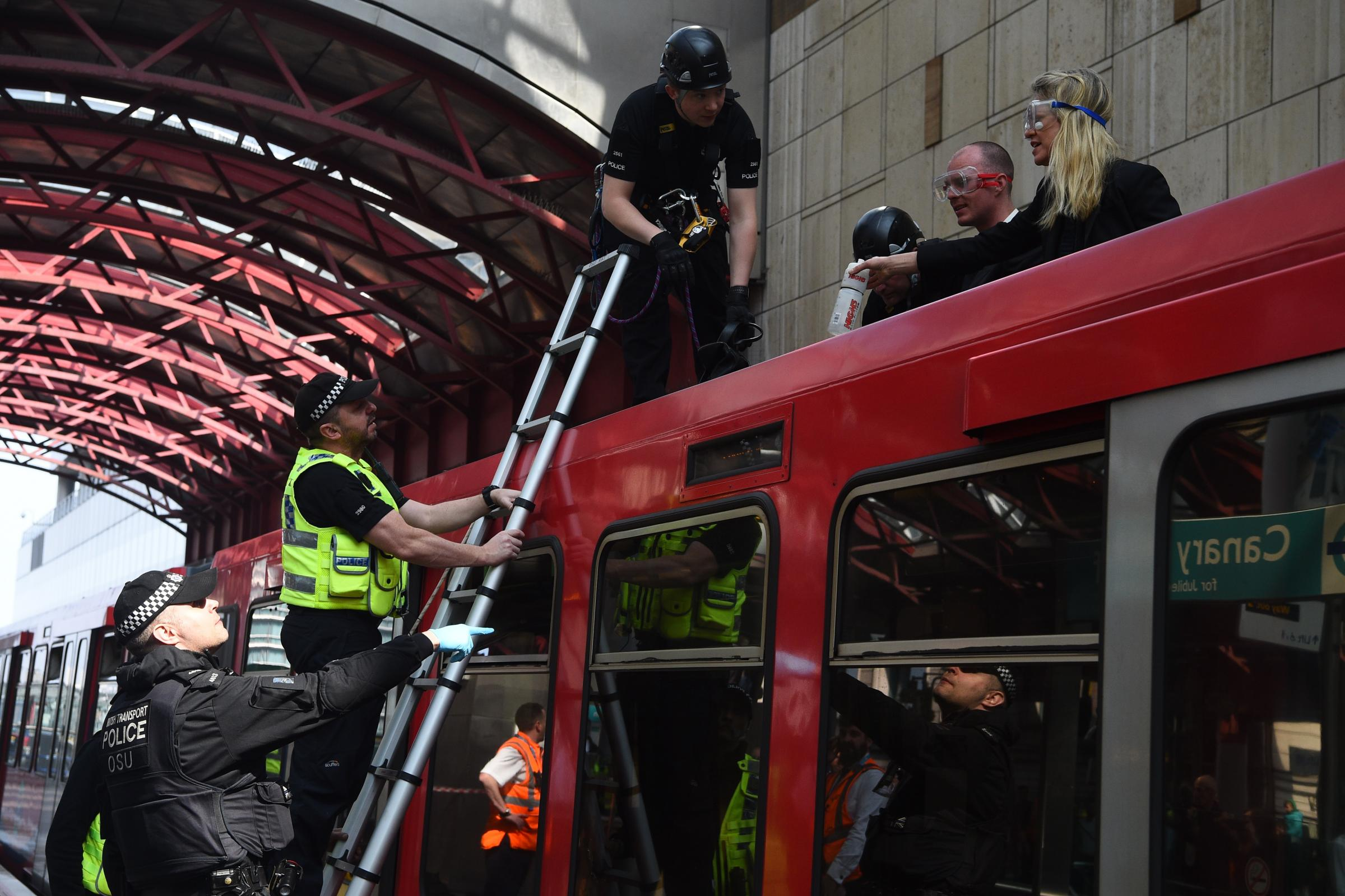 Police remove climate change activists who climbed on top of a train